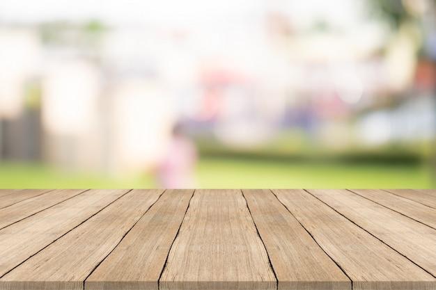 庭で背景をぼかした写真の上の木のテーブルトップ