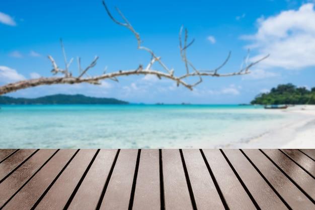 ぼやけた枝の海のビーチの白い砂の滑らかな木のテーブルトップ