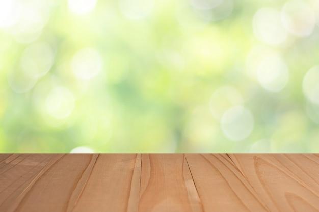 あなたの製品をモンタージュするための庭のぼやけた緑の背景に木製のテーブルトップ