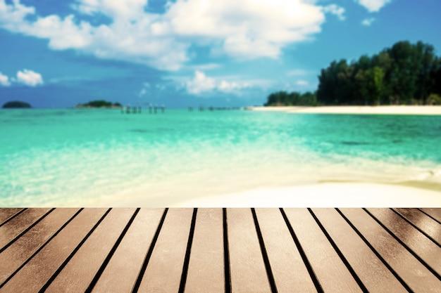 アンダマン海のぼやけた海のビーチの白い砂の上の木製のテーブルトップ