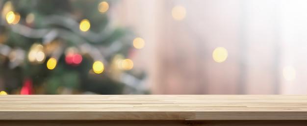 Деревянная столешница на фоне красочных боке из украшенной елки