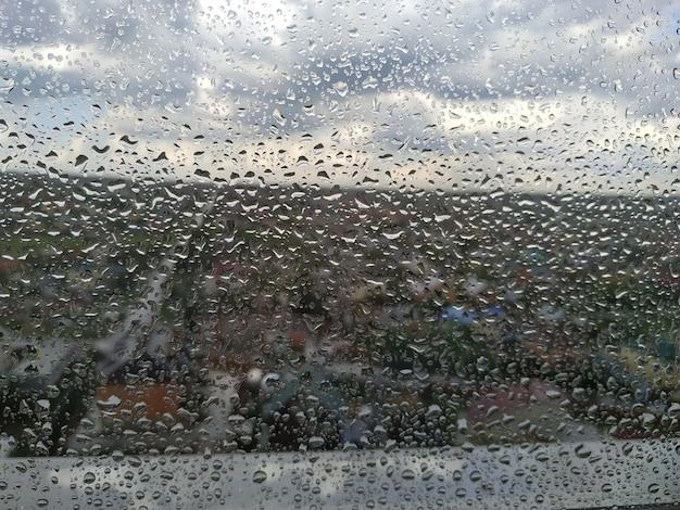 투명한 창에 있는 빗방울 위의 나무 탁자 - 제품을 전시하거나 몽타주하는 데 사용할 수 있습니다.