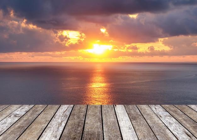 日没の海の上の日差しの上の木製のテーブルトップ