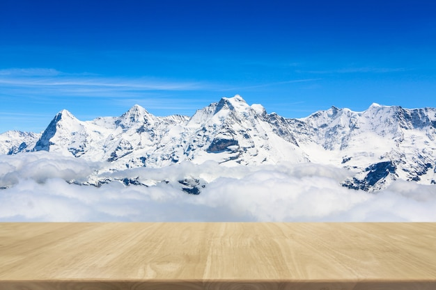 Wood table top and snow mountain background - can used for display or montage your products.