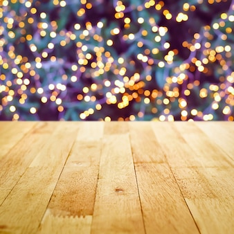 Wood table top with bokeh from decorative light on christmas tree in background