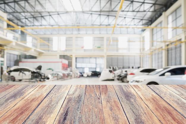 자동차 수리 서비스 센터 인테리어와 나무 테이블 탑 배경을 흐리게. 몽타주 자동 제품 디스플레이를 만듭니다.