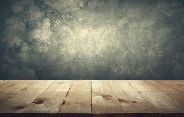 Wood table top with vintage grunge cement wall background