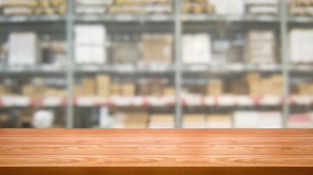 Wood table in warehouse storage blur background.