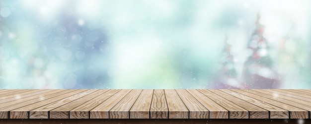 Wood table with abstract blur christmas tree and snow fall
