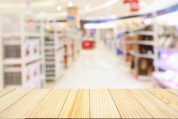 제품 선반 배경으로 추상 흐림 슈퍼마켓 통로와 나무 테이블