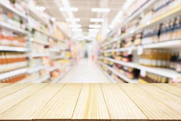 추상 흐림 슈퍼마켓 할인 매장 통로와 조미료 소스 제품 병 선반과 나무 테이블