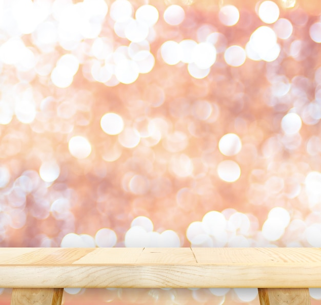 Wood table with bokeh pink sparkling background,empty room for display your product