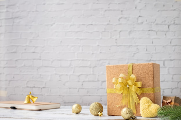 Wood table with gift box on white brick wall texture background.