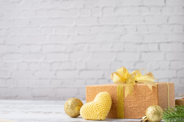 Wood table with gift box and yellow heart shaped symbol on white brick wall texture