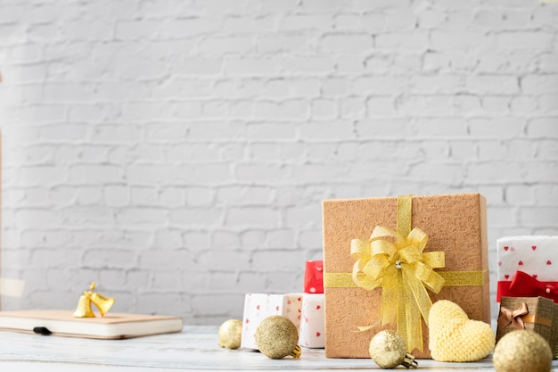Wood table with gift box and yellow heart on white brick wall texture background, view from above board.