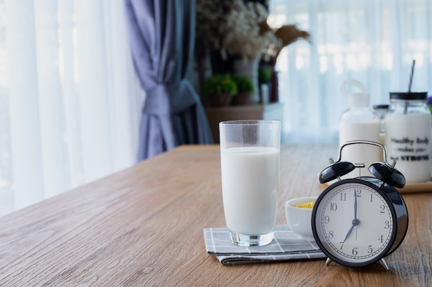 Wood table with glass of milk and retro alarm clock in living room.