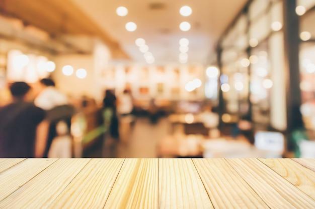 사람들이 추상 defocused 흐림 배경과 레스토랑 카페 또는 커피 숍 인테리어와 나무 테이블