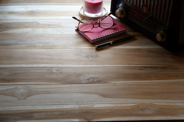 Wood table with vintage radio, red note book and copy space