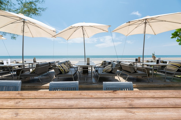 Wood tabletop on dining table with umbrella on the beach