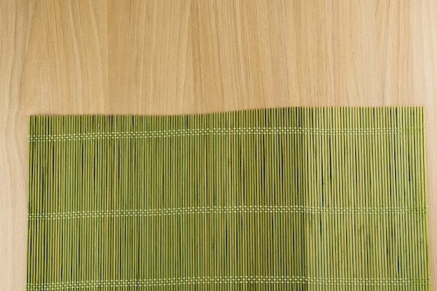 Wood texture. rustic wood with a green bamboo mat. top view.