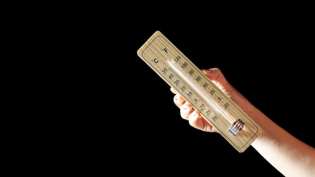 Wood thermometer calibrated in degrees celsius and fahrenheit in hand. - concept of global warming and weather.