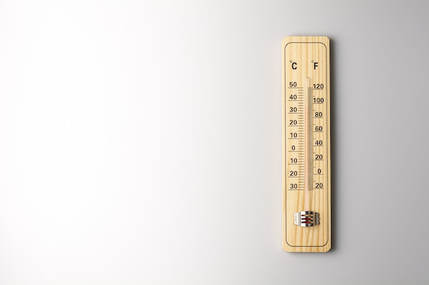 Wood thermometer calibrated in degrees celsius and fahrenheit on white background. - concept of global warming and weather.