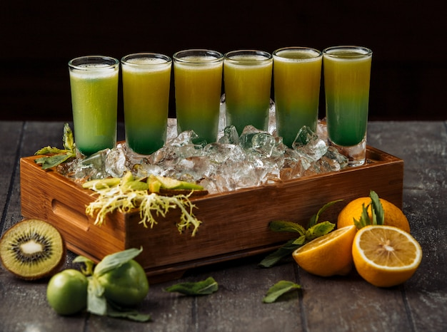 Wood tray of kiwi and orange shotes served in ice cubes