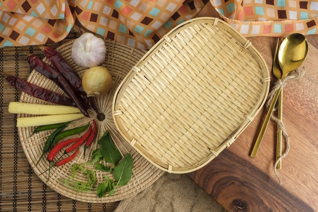 Wood tray with thai herbs and spoon and fork with free space for text background