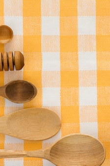 Wood utensils at table checked napkins background