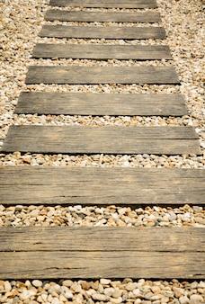 Wood walkway on stone in the garden.