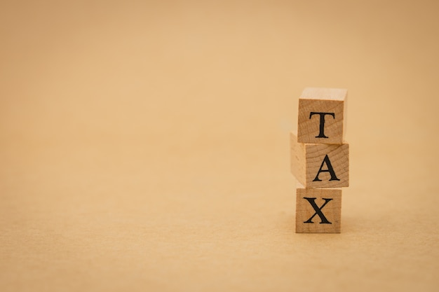 Wood word tax standing on background isolate. using as background business concept