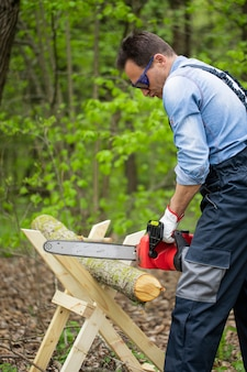 Woodcutter in working uniform sawing tree trunk on sawhorse with electric saw