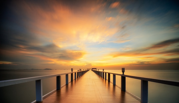 Wooded bridge by the sea with sunset sky
