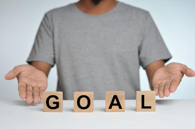 単語の目標と背景として立っている人の樹木が茂った立方体ブロックビジネス目標