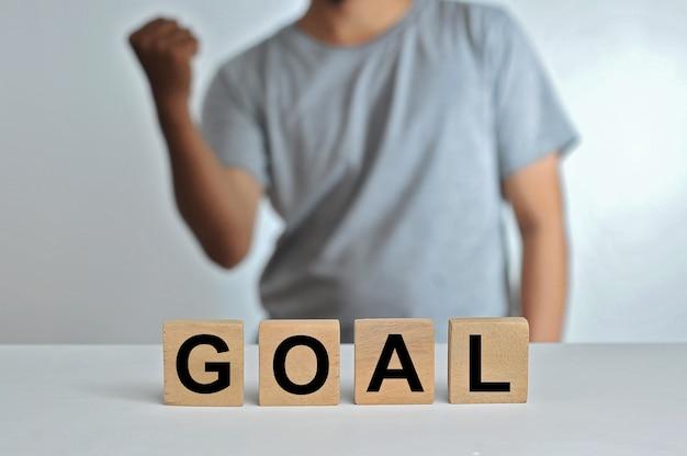 単語の目標を持つ背景として立っている人の樹木が茂った立方体ブロック