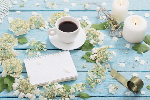 一杯のコーヒーと青いwoodem背景に白い花を持つ美しい構図