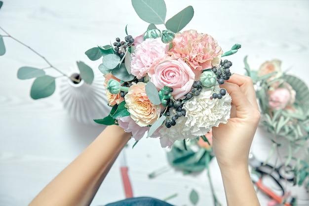 平面図は、花と花束を配置する女性の花屋の画像をトリミングして、白いwoodemの背景にツールを使用します。花の配達。コピースペース。職場と専門家のコンセプト