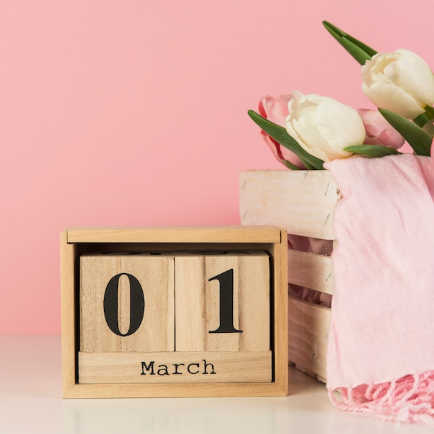 Wooden 1st march calendar near the crate with scarf and tulips against pink background