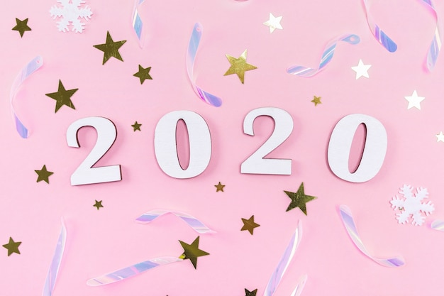 Wooden 2020 numbers and christmas decorations, confetti, stars and snowflakes