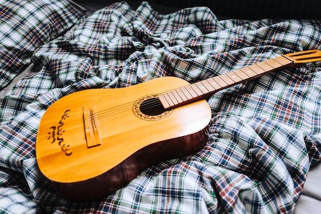 ベッドの上の木製のアコースティックギター。