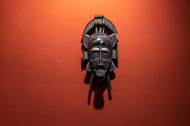 石の壁、タンザニア、アフリカの木製のアフリカのマスク。閉じる