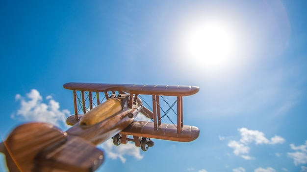 The wooden airplane fly on the background of a bright sun