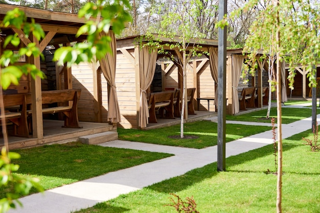 Wooden alcove gazebo in suburbs countryside golf club. the place for leisure longe, deck chairs. kinds on the playground bouncing and jumping on the trampoline in the back yard