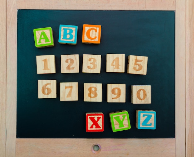 Wooden alphabet blocks with letters and numbers on wooden board