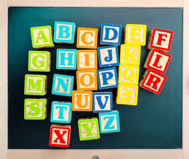 Wooden alphabet blocks with letters on wooden board