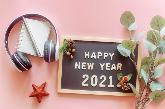 新年あけましておめでとうございます2021、葉、赤い星、トップビューのヘッドフォンの言葉で木製の文字板に木製のアルファベットが平らに横たわっていた。新年の挨拶のコンセプト。