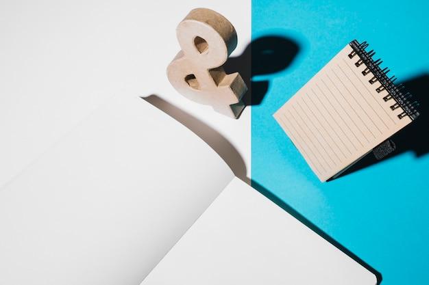 Знак деревянного амперсанда; спиральный блокнот и пустая белая страница на двойных обоях