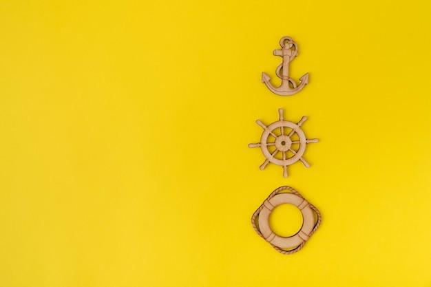黄色の背景に木製のアンカー、ステアリングホイール、救命浮輪。スペースをコピーします。