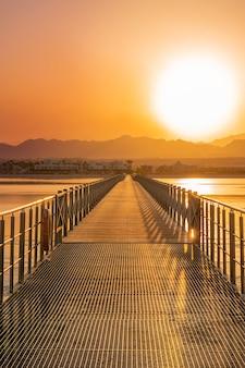 Деревянный и металлический мост, дорога или понтон, ведущие к ярко-оранжевому закату над пустынными горами
