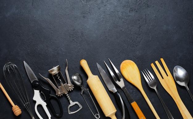 나무 및 금속 주방 용품. 요리 도구. 어두운 배경. 평평하다. 공간 복사